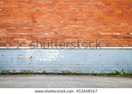 Abstract empty urban background, old red brick wall with gray tiling decoration near asphalt road