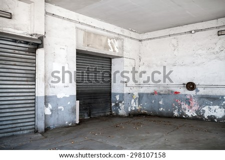 Abstract empty white interior of old automotive garage with asphalt pavement and closed metal gates - stock photo