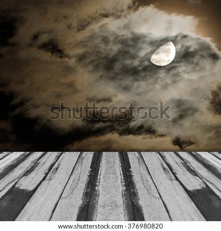 Abstract empty wooden interior room with moon and clouds in a cloudy night image on the wall - stock photo