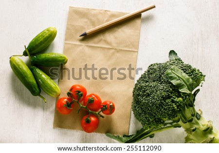 Abstract fresh organic vegetables on vintage white table food background. Healthy food from garden and paper for notes.Project healthy living. - stock photo