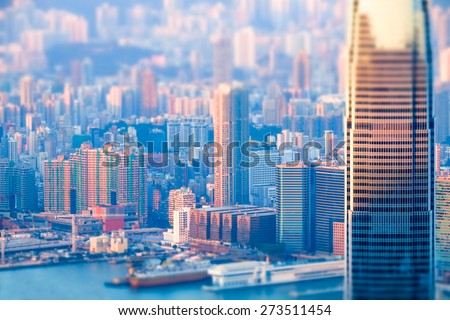 Abstract futuristic cityscape with modern skyscrapers. Hong Kong aerial view evening panorama. Tilt shift effect - stock photo