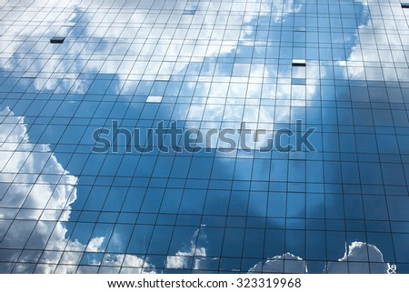 Abstract glass building reflecting clouds and blue sky - stock photo