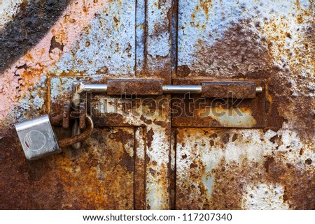 Abstract grungy metal surface and  lock on rusty iron door - stock photo