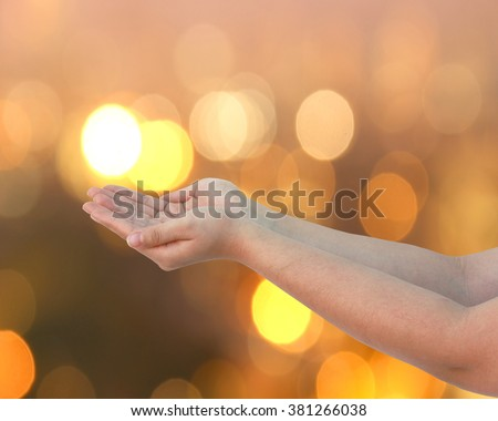 abstract Hand with a golden background bokeh. Pray for Christians. Prayer to bless our world.  - stock photo