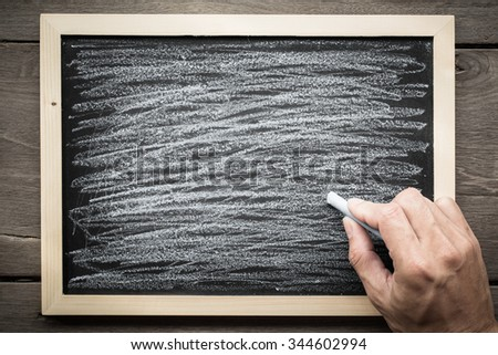 abstract Hand with chalk and black board  - stock photo