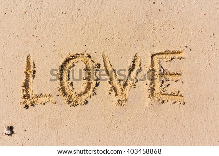 "Abstract hand writing on the sand; the word ""LOVE"""