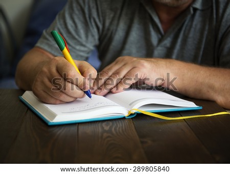 Abstract hands writing on the paper - stock photo