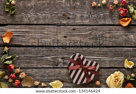 Abstract holiday frame with rose petals and dried flowers and heart shaped gift box on old wooden plates. - stock photo