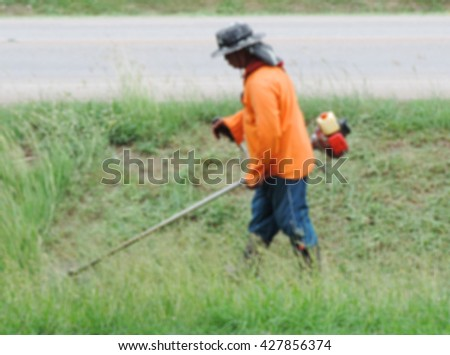 Abstract image blurred of worker of a garden cuts off a grass. The man in a uniform of the general worker works at a lawn. Work of municipal services on improvement of territories.           - stock photo