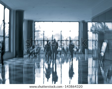 abstract image of a business people seating and walking in the lobby in intentional motion blur and a blue tint - stock photo