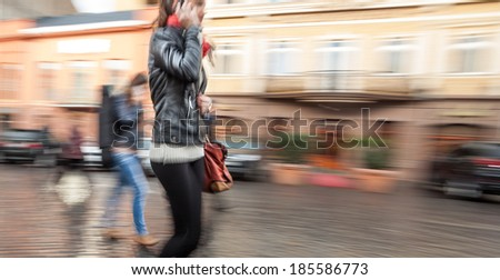 Abstract image of a young woman talking on a mobile phone on a city background. Intentional motion blur
