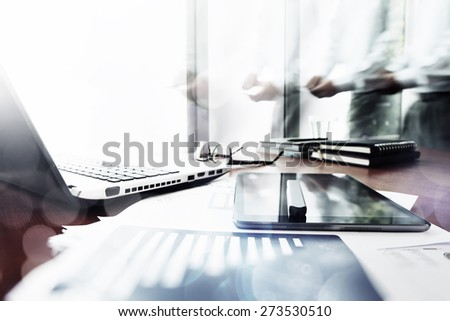 Abstract Image of business documents on office table with smart phone and digital tablet and man working in the background - stock photo