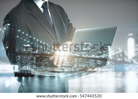 Abstract image of caucasian man using laptop on city background. Double exposure. Communication concept