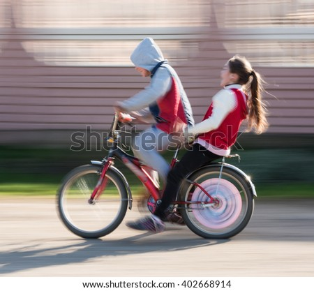 Abstract image of children riding a bike. Intentional motion blur - stock photo