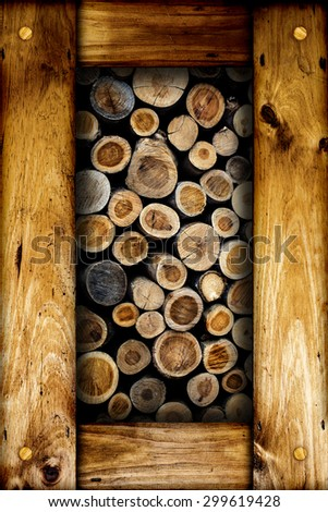 Abstract image of dry cut firewood logs in a pile inside a wooden frame. - stock photo