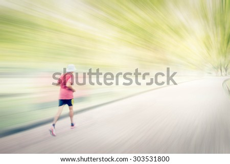 Abstract image of man jogging  in the park,. Motion blur effect. - stock photo