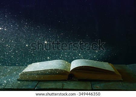 abstract image of open antique book on wooden table. selective focus. retro filtered and toned with glitter overlay - stock photo