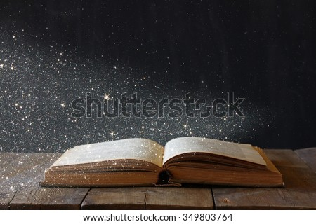 abstract image of open antique book on wooden table. selective focus. retro filtered with glitter overlay - stock photo