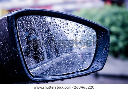 Abstract image of rain drops on car side view mirror and window. - stock photo