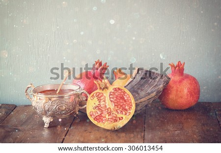 abstract image of rosh hashanah (jewesh holiday) concept - shofar, honey, apple and pomegranate over wooden table. traditional holiday symbols. glitter overlay  - stock photo