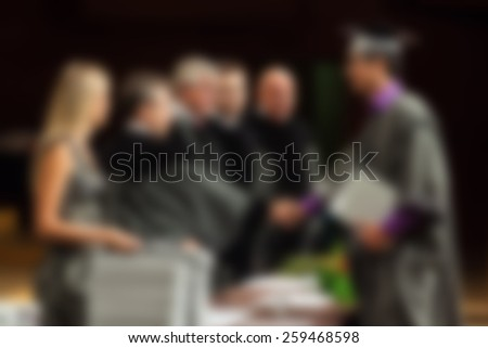 Abstract image of students receiving diploma at graduation ceremony. Intentionally blurred in post processing.  - stock photo
