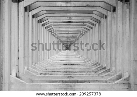 Abstract image of support beams under an old aqua-duct creating a unique ongoing repetitive design into the distance - stock photo