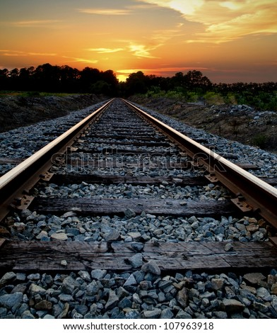 Abstract journey concept of a railroad heading into a sunset. - stock photo