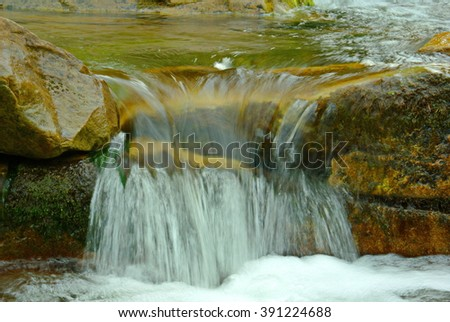 Abstract landscape of the fast flowing water in the mountain river. Light reflection on the turbulent water flow. Water captured with motion blur  - stock photo