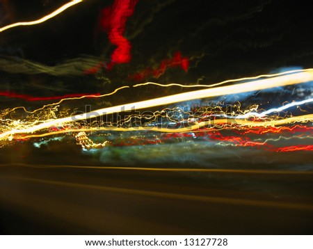 Abstract light trails captured from cars, signs, and other landmarks. - stock photo