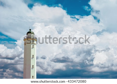 Abstract lighthouse at the seashore with cloudy blue sky - stock photo