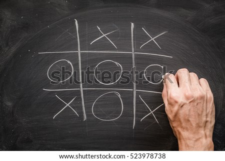 Abstract man hand on Tic Tac Toe Game Competition. XO Win Challecge Concept on black board