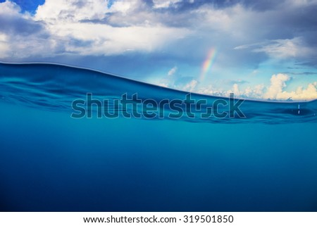 Abstract marine design template. Cloudy sky with rainbow splitted by waterline. Blue deep ocean. - stock photo