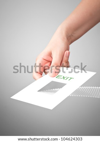Abstract metaphor of escape, exit and solution to the problem. White card  in the female hand with stairway and text label