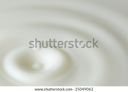 Abstract milk splash with drop still coming down - stock photo
