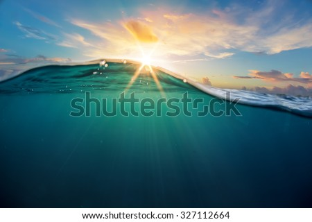 Abstract ocean design template with underwater part and sunset skylight splitted by waterline. Beautiful clouds and bright sun over sea water. - stock photo