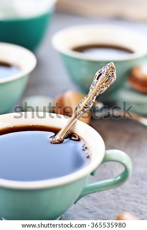 Abstract of a closeup of a teaspoon in a cup of coffee with extreme shallow depth of field with selective focus on spoon. - stock photo