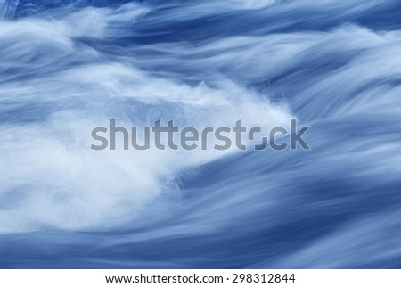 Abstract of a swiftly moving stream in shades of blue. - stock photo