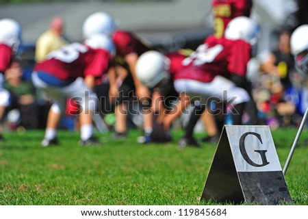Abstract of American youth football goal marker on the line with out of focus players in the background playing the game. - stock photo