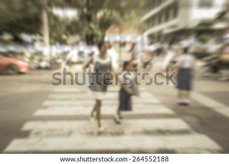 Abstract of blurred schoolchild with mother walk crossing the street - stock photo