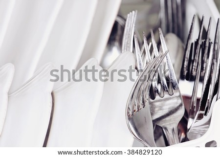 Abstract of clean forks and dishes inside of a dish washing machine. Extreme shallow depth of field with selective focus on fork. - stock photo