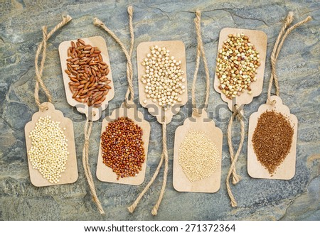 abstract of healthy, gluten free grains (quinoa, sorghum, brown rice, teff, buckwheat, amaranth, millet) - top view of paper price tags against a slate stone - stock photo