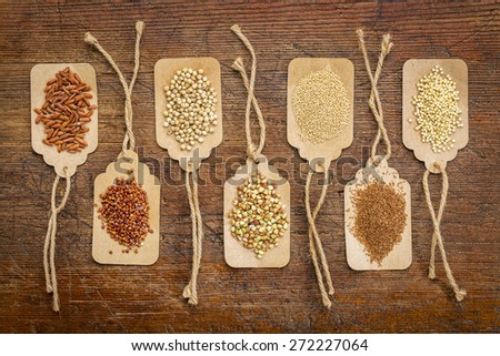 abstract of healthy, gluten free grains (quinoa, sorghum, brown rice, teff, buckwheat, amaranth, millet) - top view of paper price tags against rustic wood - stock photo