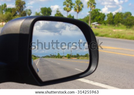 Abstract of the beautiful blue sky in the car mirror on nature road