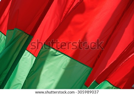 Abstract of the fabric. Red-green flags fluttering in the wind.