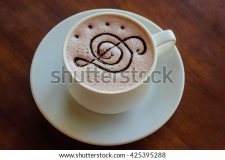 Abstract of top view of music note G Clef symbol foam texture on hot chocolate in white cup in vintage tone style : food concept - stock photo