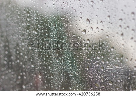 Abstract of water droplets on car mirror on raining day - stock photo