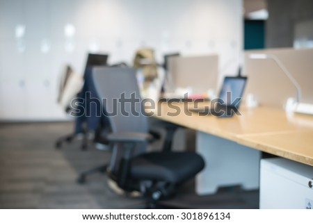 Abstract office blur background with wooden desk, chair with laptop/pc and display