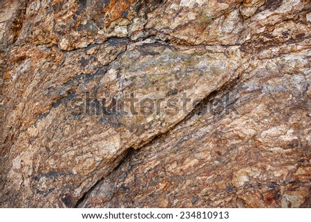 Abstract pattern of a natural rock in brown, beige and blue. In the middle slightly bright green growth. Taken in La Gomera, Canary Islands, Spain.