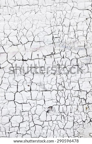 abstract pattern of cracks in old and grungy white washed brick wall