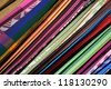Abstract patterns of a rainbow of colors and angles are formed by these handmade hammocks hanging for sale at the outdoor craft market in Otavalo, Ecuador - stock photo